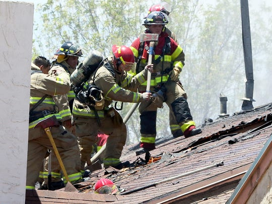 El Paso firefighters open a hole in the attic space