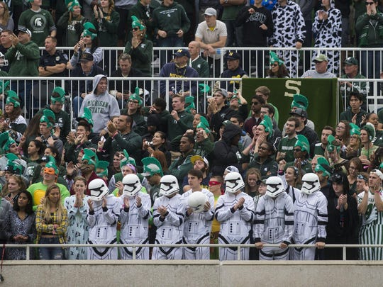 Michigan State students dress in Halloween costumes while attending a game against Michigan in East Lansing on Saturday. The Spartans put a scare into Michigan, but fell, 32-23.
