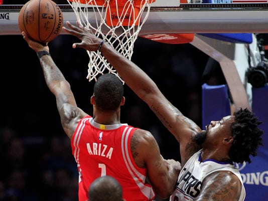 Houston Rockets forward Trevor Ariza, left, shoots against Los Angeles Clippers center DeAndre Jordan, right, during the first half of an NBA basketball game in Los Angeles, Monday, Jan. 18, 2016. (AP Photo/Alex Gallardo)