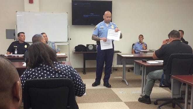 Guam Police Department Chief Joseph I. Cruz holds up printouts of the proposed fitness standards for peace officers at the Peace Officer Standards & Training Commission meeting on July 6, 2017.