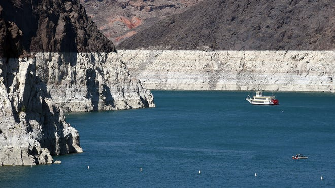 Boats travel in front of mineral-stained rocks near the Hoover Dam. North America's largest man-made reservoir has reached critically low levels.