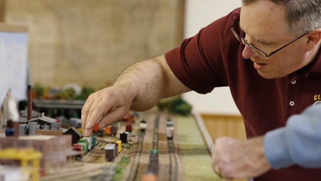 Clipper City Model Railroad Club members Phil Stangel, left, and Bill Zoerb are getting the train sets ready for the annual spring open house.