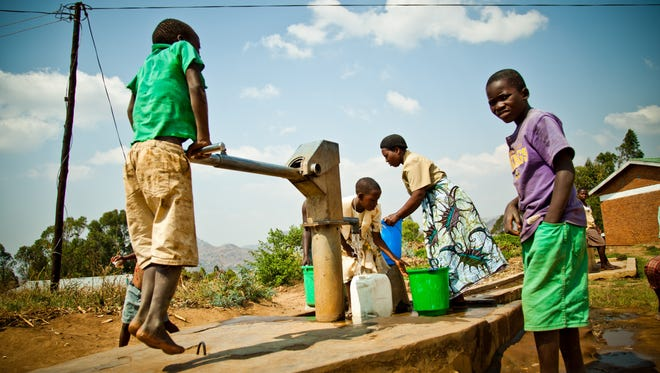 Children retrieve water from a well in Lizulu, Malawi. Funds to build the well were raised by nonprofit coffee shop The Well, which will open a location in Fishers this August.