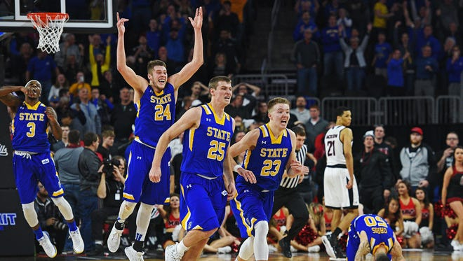 SDSU's Mike Daum (24), Lane Severyn (25) and Reed Tellinghuisen (23) celebrate their 79-77 win over Omaha in the Summit League Tournament men's championship game Tuesday, March 7, 2017, at the Denny Sanford Premier Center in Sioux Falls.