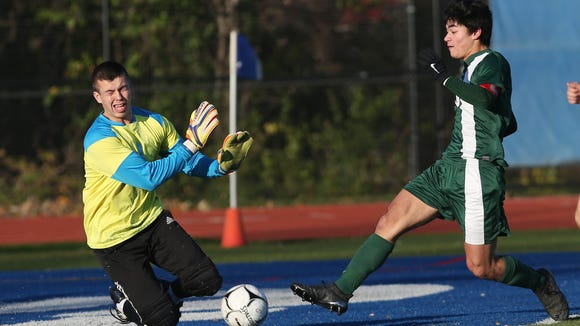 From right, Schechter's Miles Ogihara (10) fires a shot on Seward goal keeper Bobby Verblaauw during the boys soccer regional semifinal at Middletown High School Oct. 31, 2017.