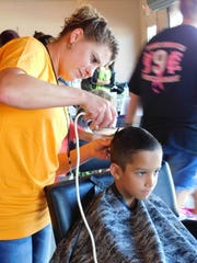 Dezi Smith, 11, gets a haircut from Chelsea Becton