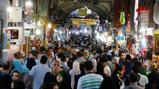 Iranians shop in Tehran's ancient Grand Bazaar on July 11, 2016. A year ago, a nuclear deal with world powers led Iranians to dream of an end to economic hardship.