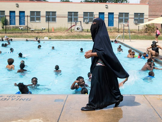 Tahsiyn Ismaa'eel, director of the Darul-Amaanah Academy, watches over swimmers from her academy on Thursday, July 12, 2018, at Foster Brown pool in Wilmington.