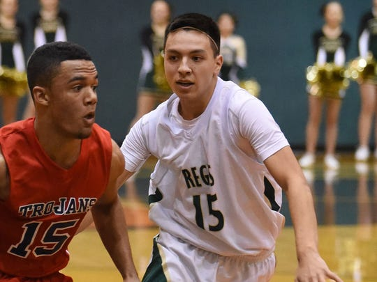 Regis's Bryce Piete guards Kennedy's Bishop Mitchell as the Rams defeat the Trojans 49-40 in a Tri-River Conference game on Friday, Jan. 23, 2015.