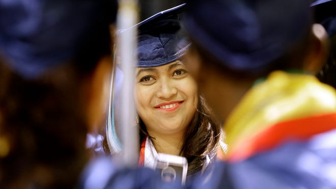 Windhy Natalia Kana smiles after taking a photo of her fellow graduates at the Northeast Wisconsin Technical College commencement in May 2016. Wisconsin's technical colleges are looking for ways to keep people enrolling in classes at a time when a bright job market, bolstered by a strong economy, has made it tougher to recruit students who have joined the workforce.