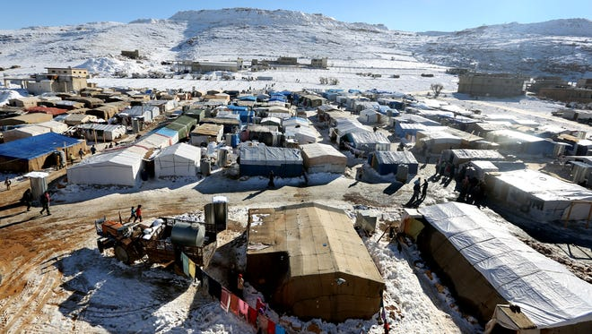 Syrian refugees walk outside their tents at a refugee camp in the eastern Lebanese border town of Arsal, Lebanon, Dec. 15, 2013. Tens of thousands of impoverished Syrian refugees living in tents, shacks and unfinished buildings throughout Lebanon face a miserable winter as aid organizations scramble to meet their needs, constantly overwhelmed by ever-more Syrians fleeing their country's war.