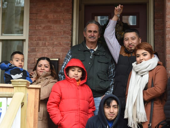 The Talamantes family waves the keys to their new home