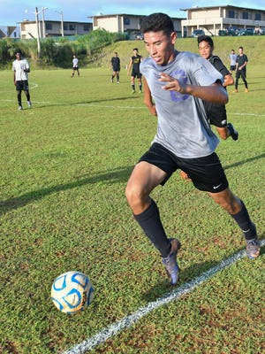 In this Nov. 23 file photo, Xavier Naputi of the George Washington Geckos advances the ball down the sideline against the Tiyan Titans in an Independent Interscholastic Athletic Association of Guam Boys Soccer League match.
