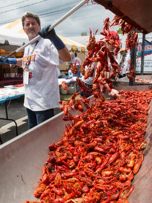 Henry Guarino of Baton Rouge, LA, loads up the trough with boiled crawfish during the Crawfish Festival in Augusta, NJ, on Saturday, May 30, 2015.