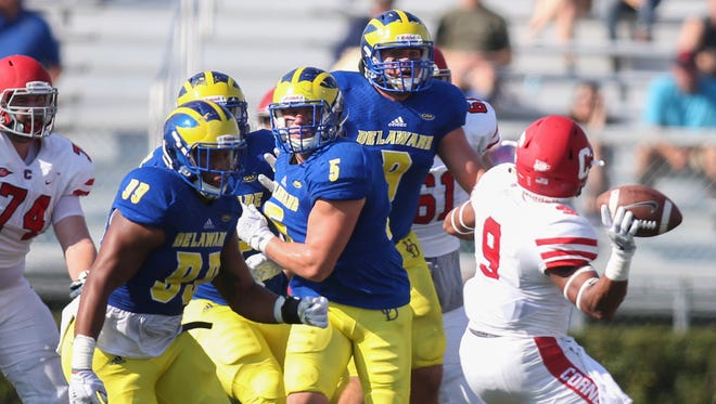 Cornell running back Chris Walker rears back to throw a  pass - intercepted by Delaware - in front of Blue Hens (from left) Cam Kitchen, Charles Bell and Troy Reeder in the first quarter of Delaware's 41-14 win at Delaware Stadium Saturday.