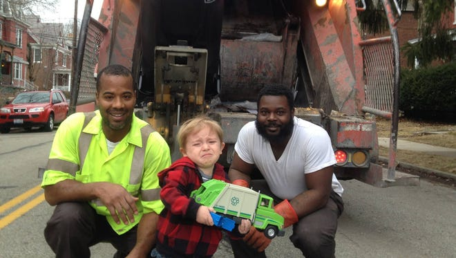 Two-year-old Quincy Kroner from Northside posing with his heroes, Mark Davis, left, and Eddie Washington, the local garbage men.