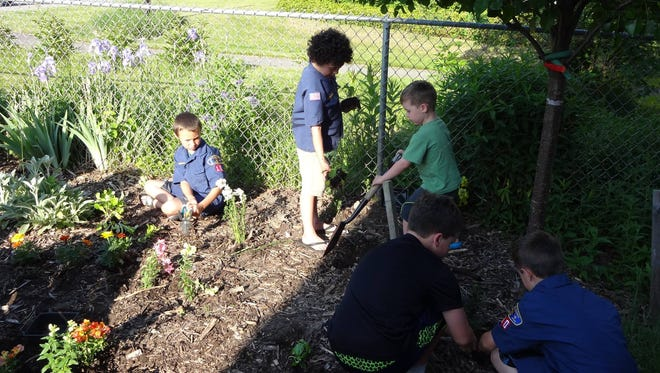 Members of Cub Scout Pack #10 help to plant and weed at the Children's Garden at Groton Public Library.