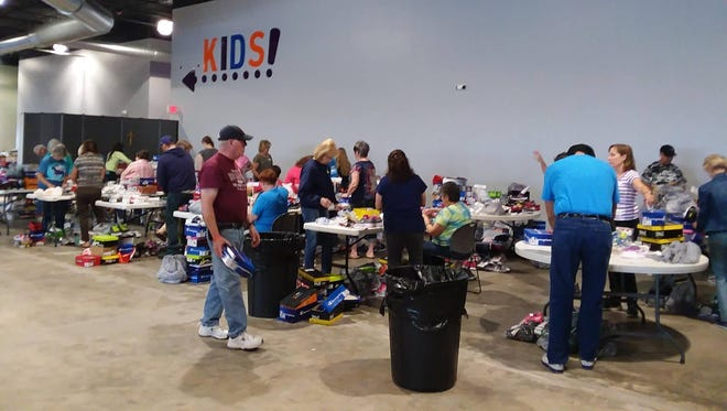 Volunteers help sort Soles 4 Souls shoes at Mesilla Park Community Church earlier this month. The shoe giveaway event will be held Saturday, April 1, at the church, 1040 El Paseo Road.