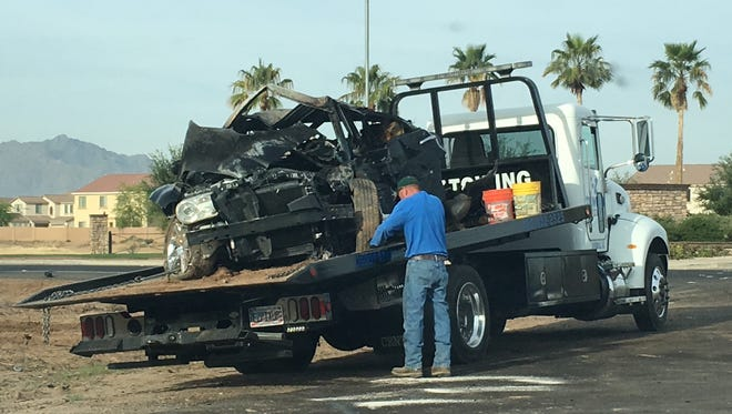 A tow-truck driver secures a vehicle that rolled, ejecting and killing the driver on April 10, 2017, near Laveen.