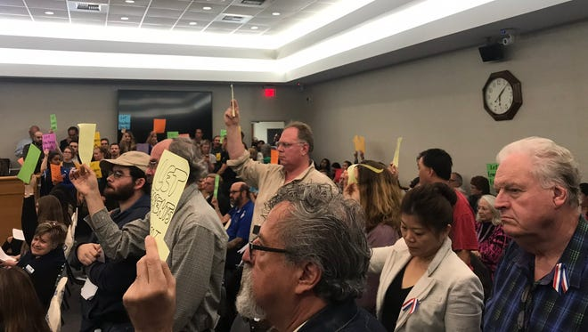 Parents, teachers and students held signs during Tuesday's contentious board meeting.