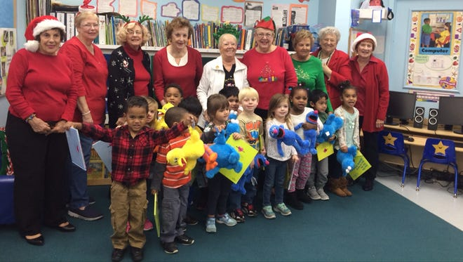 Christ Child Society of Stuart members recently took books and stuffed animals to the Dunbar Center in Hobe Sound. The adults pictured, from left, are Vicky Moran, Peggy Dombkoski, Leslie Berch, Liz McIntyre, Judy Richardson, Jane Ball, Susan Steitz, Cindy Wilson and Nedy Mead with the 3-year-old class.