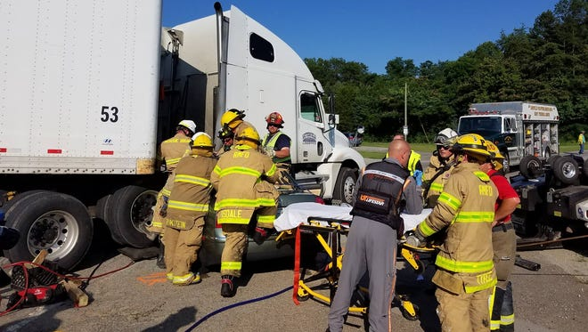 Rural/Metro firefighters work a crash involving a car and a tractor-trailer on Andrew Johnson Highway on July 3, 2018.