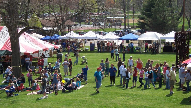 Crowds mill about the tents at Earth Gathering, the annual celebration of arts and music on the lawn of the Pump House Center for the Arts.