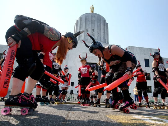 Members of the Cherry City Derby Girls wait to chase runners during the 2nd Annual Sunday Streets that took place in Sept. See them play roller derby this weekend.