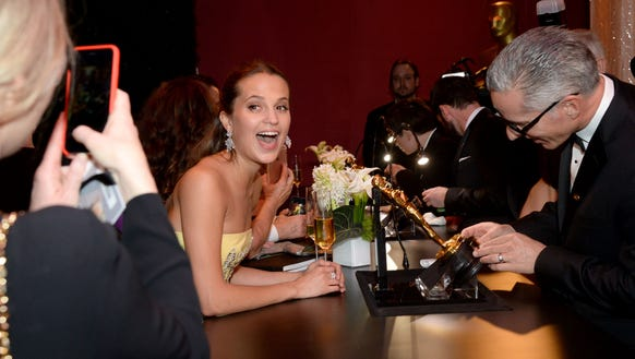 Alicia Vikander smiles wide while watching her Oscar