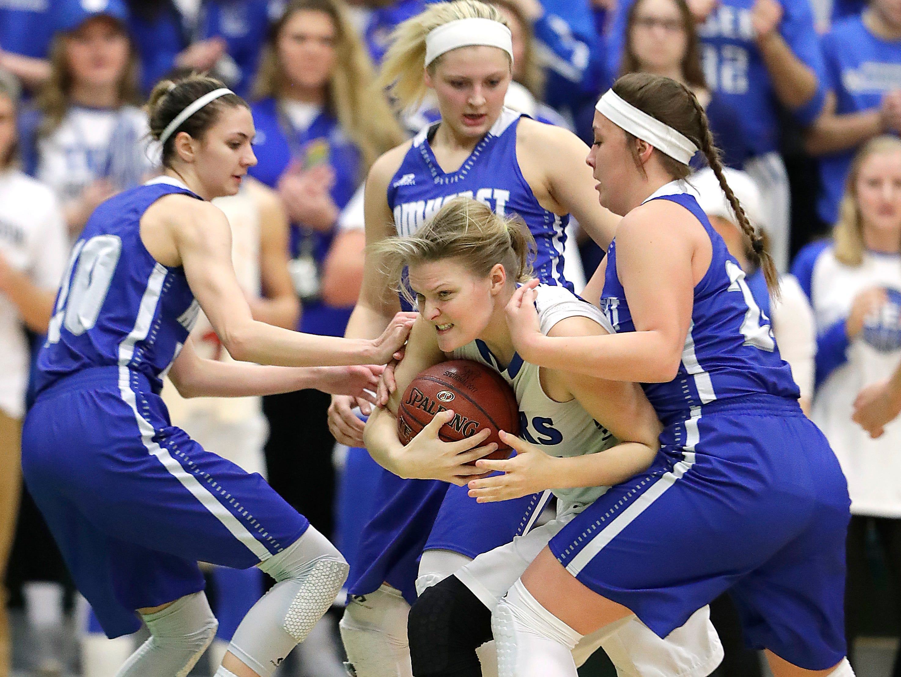 Wrightstown senior Ashley Glodowski fights for possession against Amherst defenders in a WIAA Division 3 sectional final girls basketball game at Green Bay Preble on Saturday. Glodowski is one of three six seniors for the Tigers this season.