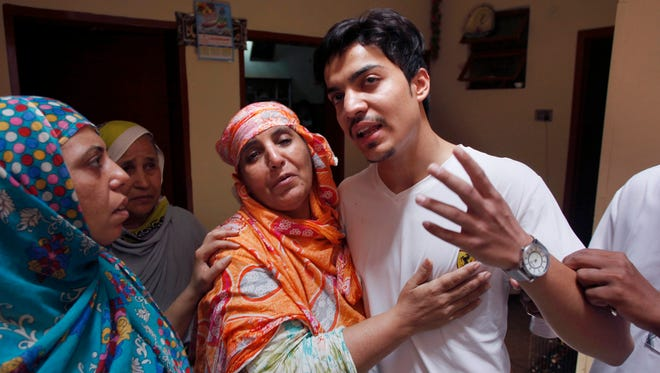 Family members comfort Hassan Khan, center, the husband of Zeenat Rafiq, who was burned alive, allegedly by her mother, at his home in Lahore, Pakistan June 8, 2016. A Pakistani woman was arrested Wednesday after dousing her daughter with kerosene and burning her alive, allegedly because the girl had defied her family to marry a man she was in love with, police said.