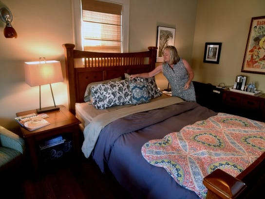 Faith McDaniel makes up one of the beds in the bed-and-breakfast she operates with her husband, Doug, in Knoxville's Fourth and Gill neighborhood Aug. 3, 2016.