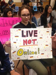 Wiktoria Jastrzebski, a freshman at Lakewood High School, holds a sign to protest the elimination of the schools German language program at the school board meeting on May 11, 2016.
