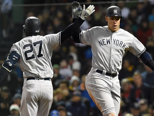 New York Yankees right fielder Aaron Judge (99) reacts with right fielder Giancarlo Stanton (27) after hitting a home run during the fifth inning against the Boston Red Sox at Fenway Park.