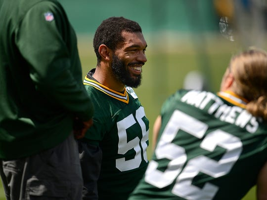 Green Bay Packers linebacker Julius Peppers (56) visits with Clay Matthews during organized team activities June 2 at Clarke Hinkle Field.