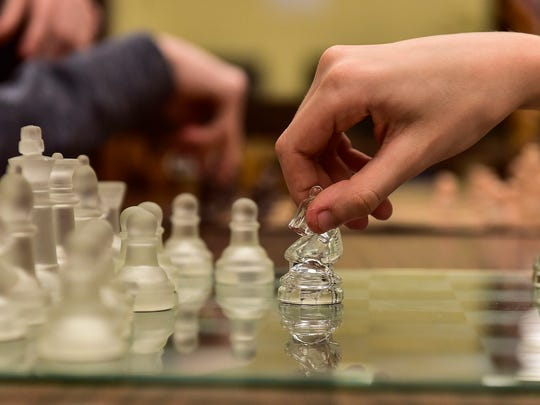 A student is reluctant to let go of the knight on the chess board after making his move during a chess game in the Ridgedale Library on Tuesday evening.