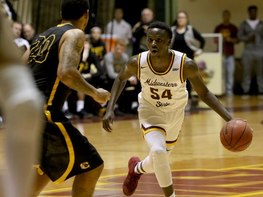 Midwestern State's Logan Hicks dribbles by Cameron's