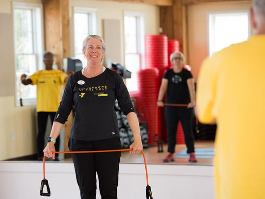 Hope Cochran, a YMCA instructor, works on stretching with her class during the LIVESTRONG workout at the YMCA.
