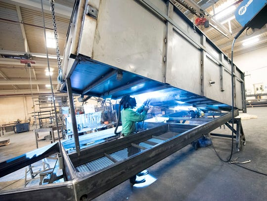 An employee welds a dump trailer at BWise Manufacturing,
