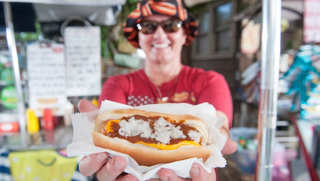 Robyn Bednar, owner of Hot Diggidy Dog in Chatsworth, displays a chili cheese dog with onions.  06.23.17