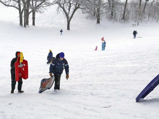 Sledders walk back up the hill while sledding at Waveland Golf Course in 2007.