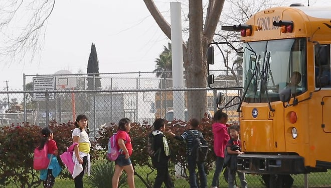 Children at the Orange Center Elementary School in Fresno board the school bus after school, March 3, 2016.