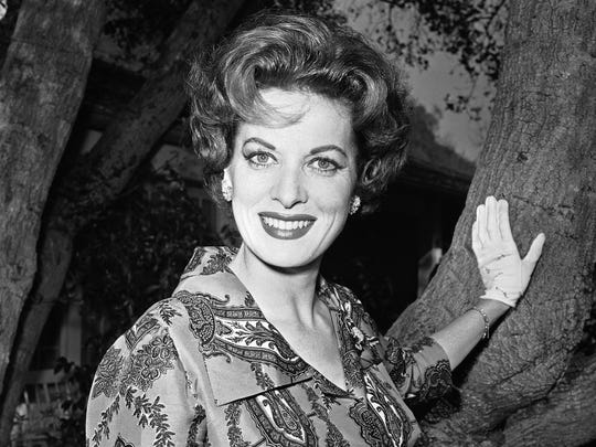 This Jan. 19, 1960 file photo shows movie actress Maureen O'Hara photographed in her front yard in Los Angeles.