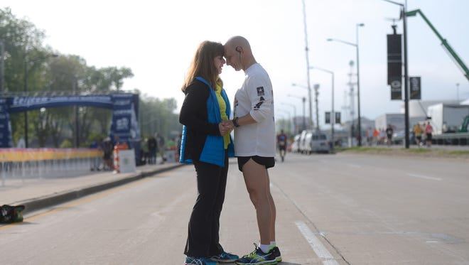 Cindy and Doug Magnin, of Oconto Falls, share a moment on Lombardi Avenue before Doug ran the half marathon at the Cellcom Green Bay Marathon on May 17, 2015.