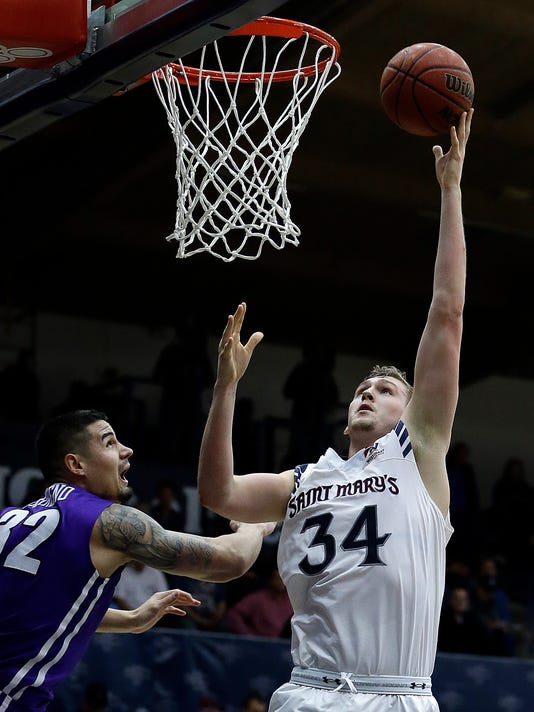 Saint Mary's Jock Landale, right, shoots over Portland's Ray Barreno during the first half of an NCAA college basketball game Thursday, Feb. 9, 2017, in Moraga, Calif. (AP Photo/Ben Margot)
