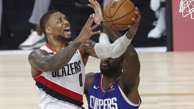 Portland's Damian Lillard (0) drives to the basket against Los Angeles' Patrick Patterson during the second half of Saturday's game at Lake Buena Vista, Fla.