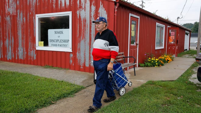 Thomas Hood carries items home to eat from the Mark of Discipleship Food Pantry in Spencer, Ind.