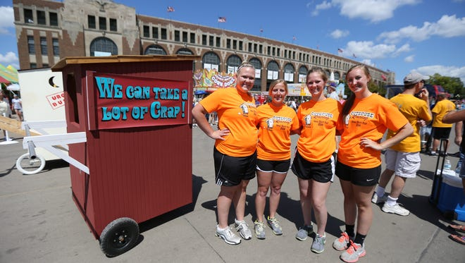 Members of the Outhouse family, from left, Abbi Outhouse, Brittnie, Amanda and Hanna Outhouse pose for a picture before the Outhouse Race at the Iowa State Fair on Tuesday, Aug. 12, 2014, in Des Moines, Iowa. Abbi and her sister Amanda, both of Defiance, and their cousins Brittnie, of Omaha, and her sister Hanna of Schleswig.