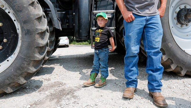 Jayden Dammann, 3, waits for a tractor ride while his father, Justin, visits with others on the family farm in rural Page County on July 19, 2014. Justin says he feels confident about the management of the family farm and one day passing it on to Jayden. His daughter Jillian says she is not sure she wants to farm, though Justin says he would welcome her into the operation if she chose that career.