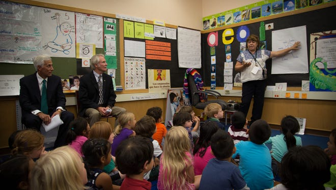 Bridger teacher Carmen Ramirez talks to her kindergarten class about vocabulary words in Spanish. Ray Davis, CEO of Umpqua Bank (left) and Gov. John Kitzhaber (right) visited the Portland school on Monday as part of a launch event for a statewide literacy campaign.